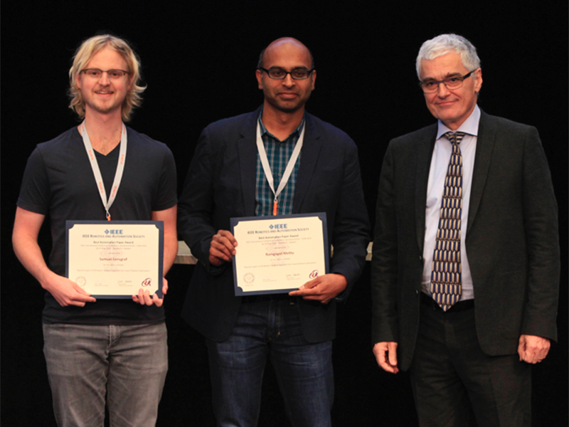Sam Lensgraf (left) and Ramgopal Mettu (center), receive their award for Best Automation Paper from award committee member Jean-Paul Laumond (right)