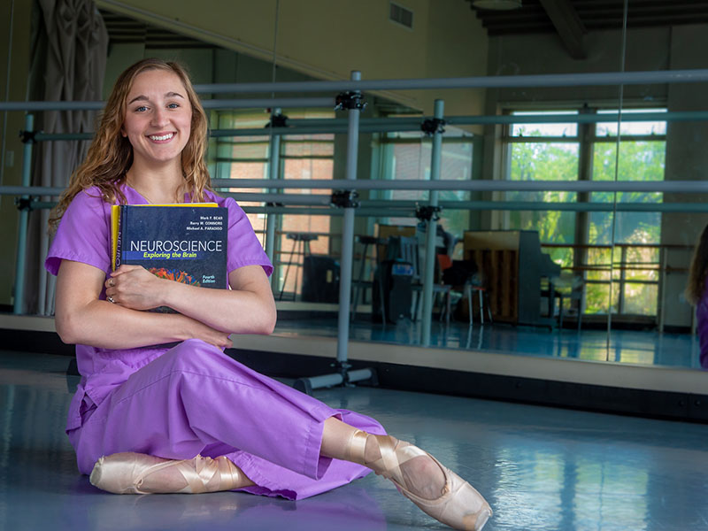 A student poses with a neuroscience book and ballet slippers, her two fields of study.