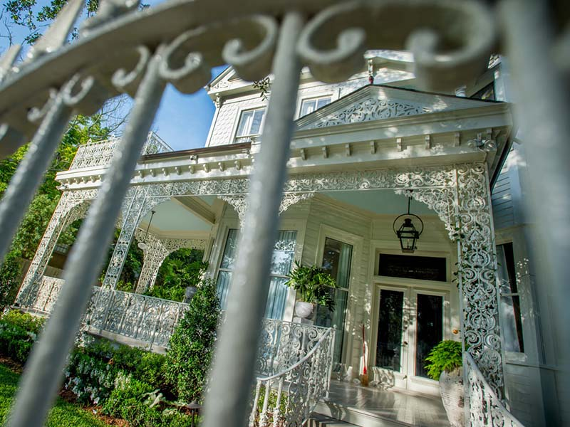 Dappled morning light accentuates the filigree iron work on a St. Charles Avenue home near the Tulane University uptown campus.