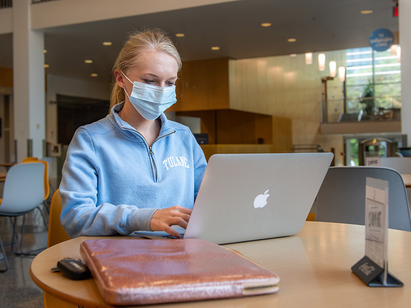 Masked student using laptop