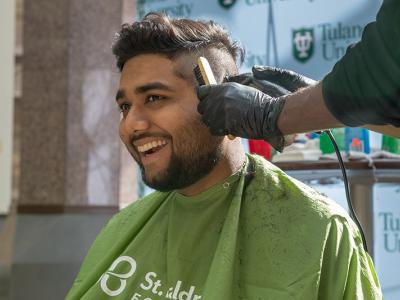 Rishawn Dindial grins as he is half way through his head shaving in barber's chair