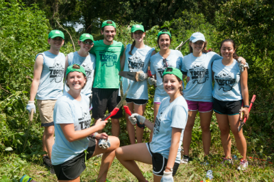 Tulane students pose for a photo at a service event. Click to play the video