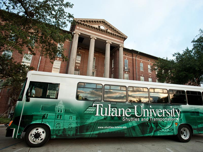 A Tulane shuttle bus is pictured parked in front of Newcomb Hall with a bright green Tulane University shuttle bus wrap covering its sides.