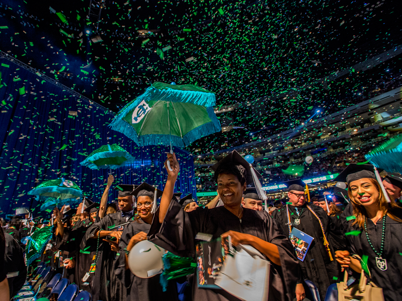 Confetti rains down on graduates holding TU second-line umbrellas