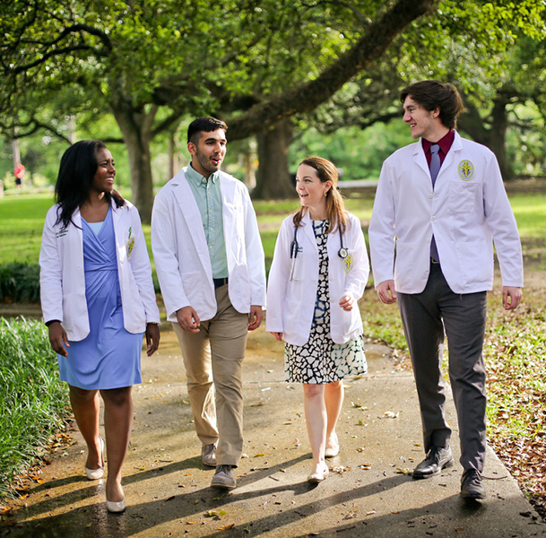 Four students in their white coats talking and walking outside