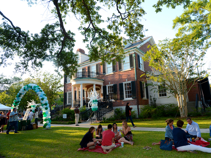 Picnickers gather on the lawn in front the Bea Field Alumni House