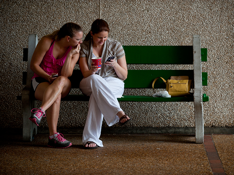 Two people on a bench looking at a smart phone