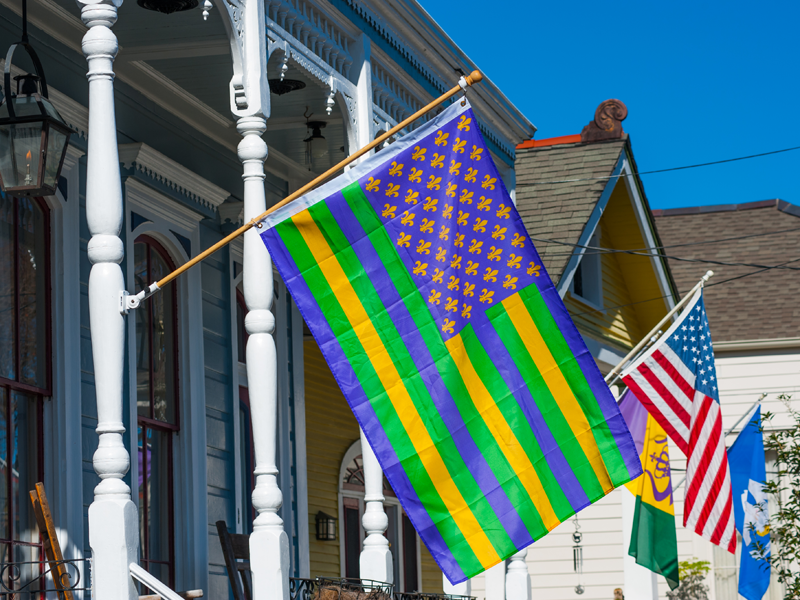 Colorful flags hang on New Orleans homes