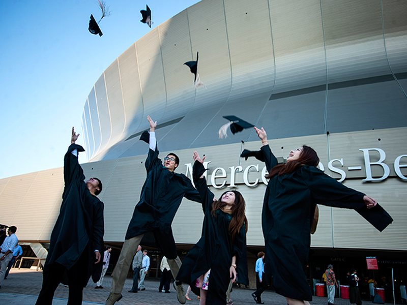Graduates throw their caps in the air outside the Mercedes-Benz Superdome