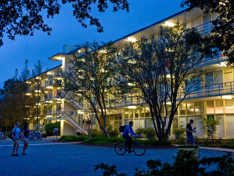 Students walk and bike past the Irby residence hall