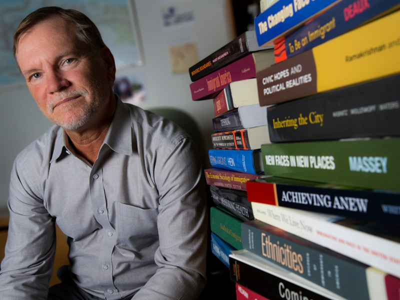 A professor sitting by stacks of books on desk
