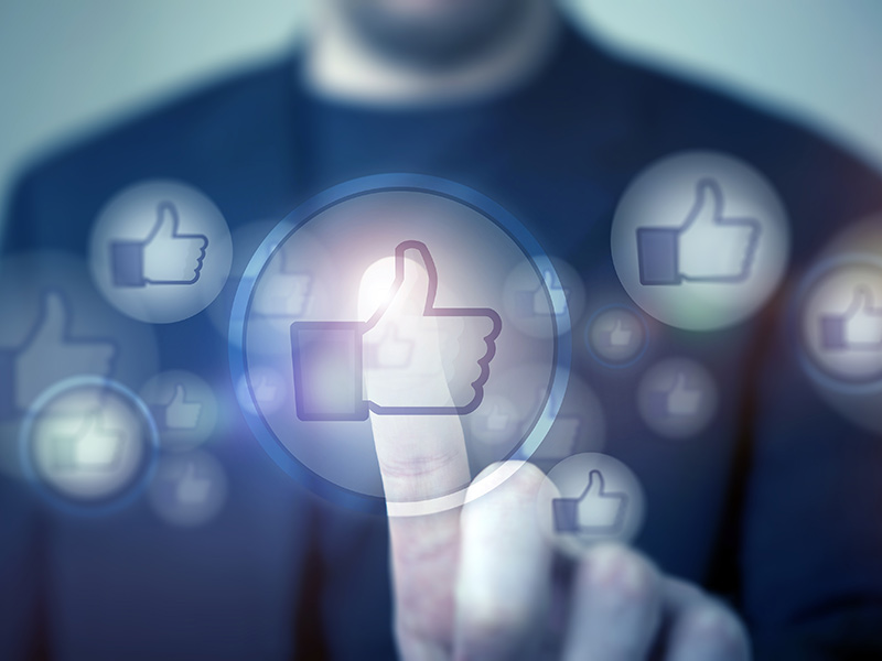 A person hitting a Facebook like button