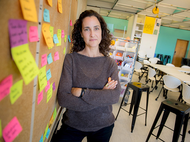 Allison Schiller,design thinking project manager for the Phyllis M. Taylor Center for Social Innovation and Design Thinking, stands in front of a board marked with post its in a classroom.