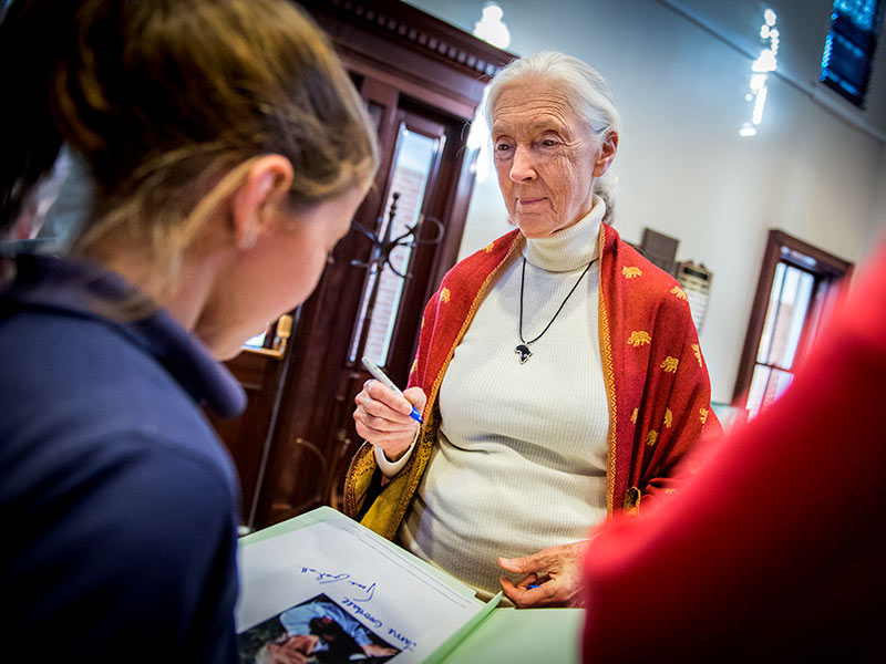 Jane Goodall signing a book for a student