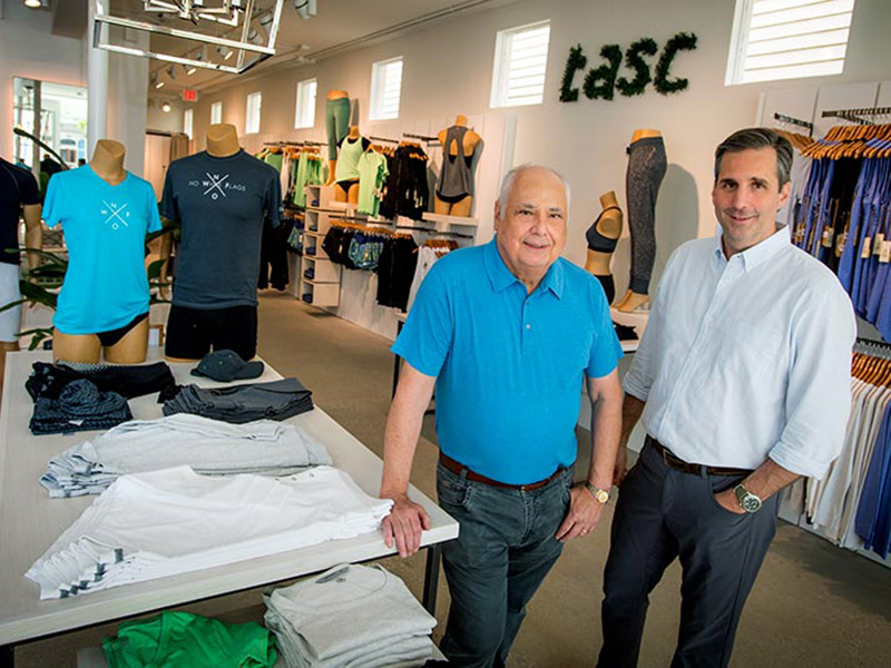 Tulane University alumnus Al Andrews and his son Todd Andrews, posing for a picture inside their store tasc Performance