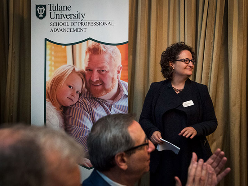 Suri Duitch, Dean of the School of Professional Advancement, looks on as the new name and plan for the school is announced at an event