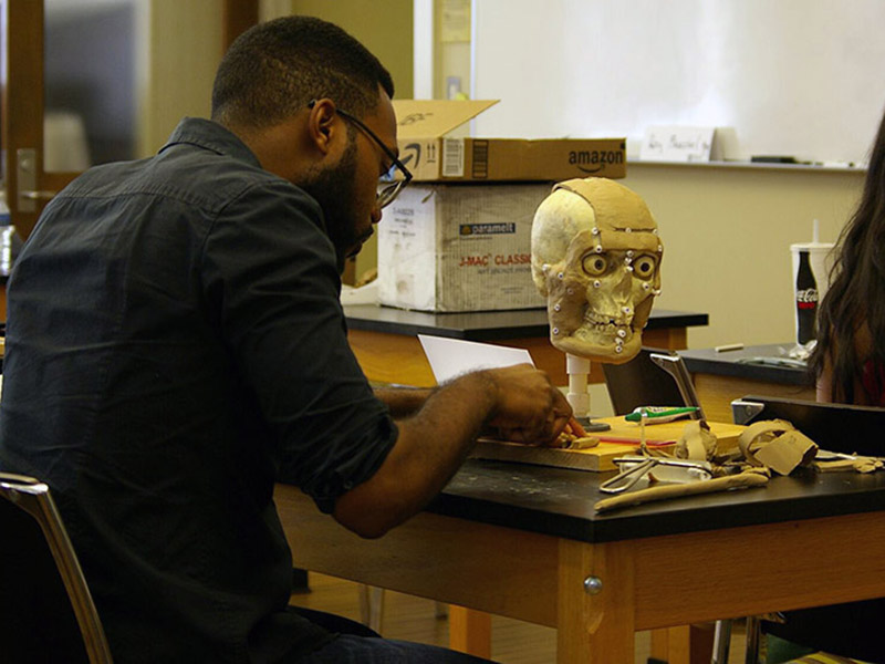 "Gregory Smith, a student in last year's course, molds ""skin"" onto a skull."