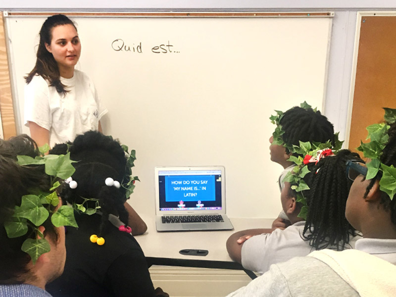 Tulane students work with students at Lafayette Academy Charter School in order to spread knowledge of and passion for Latin studies.