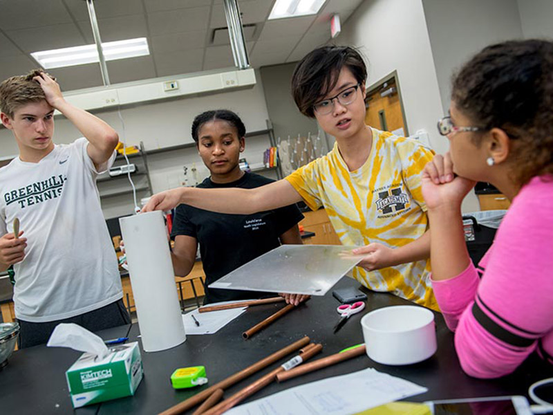 Henry Branch, Destini Renard, Jessica Xu and Asia Hentkowski, left to right, collaborate on the design and construction of a heat exchanger in a lab in Flower Hall.