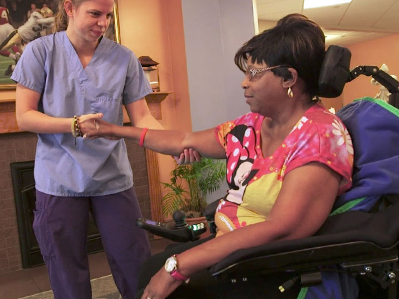 A student helps a woman with ALS.