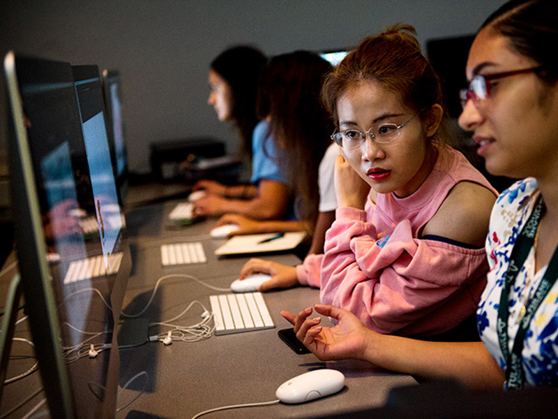 One student looks on as another student uses a computer.