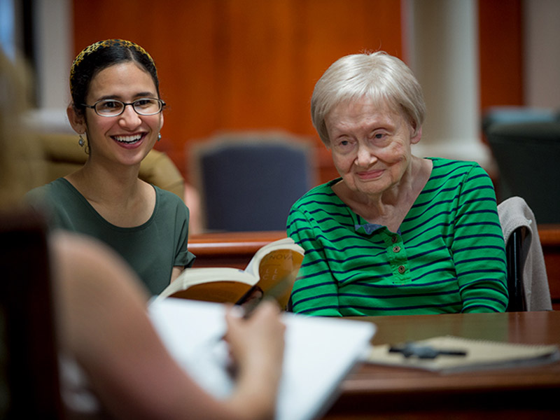 Tulane student Hanan Rimawi, left, reads to Gloria Worten, a resident of Our Lady of Wisdom Healthcare Center, while Alison Barnwell, far left, draws her portrait.
