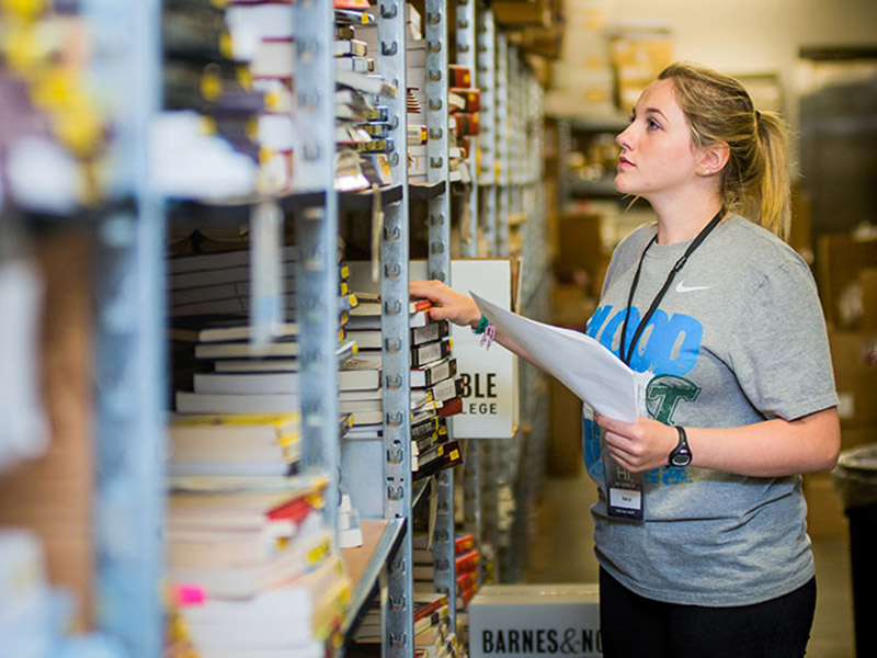 Emilie Redmann, a second-year student in the School of Liberal Arts, works in the stockroom of the Tulane University bookstore, filling textbook orders for arriving students.