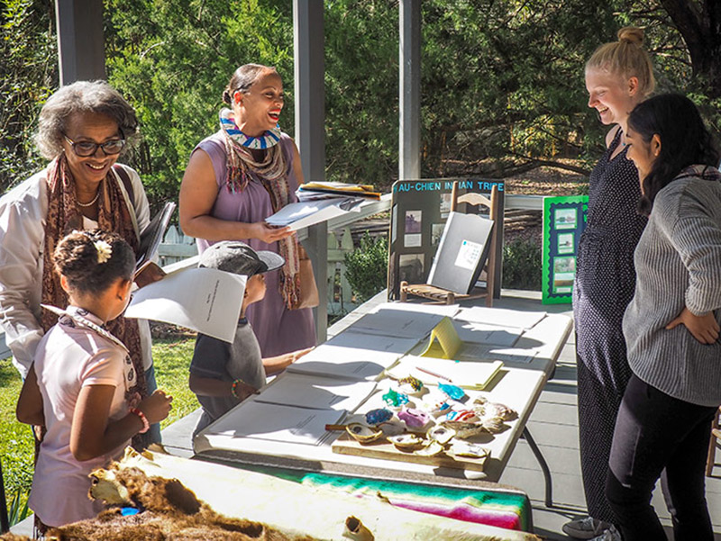 Tulane first-year students Alex Whitacre and Mirna Sanyal discuss their research projects with attendees at a Native American Heritage Day celebration on Nov. 12 hosted at Vermilionville, a living history museum in Lafayette, Louisiana.