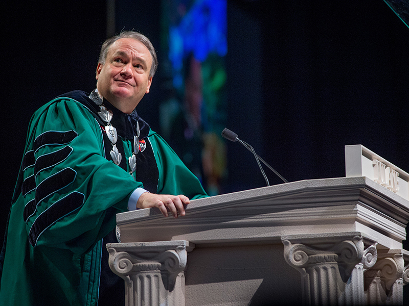 President Fitts stands at the podium during the Commencement ceremony