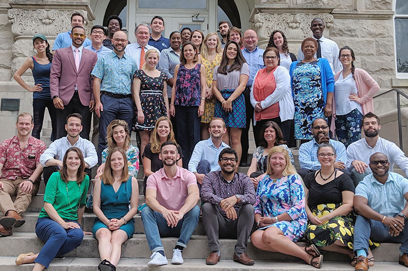 The undergraduate admissions team poses together on the steps in front their office in Gibson Hall