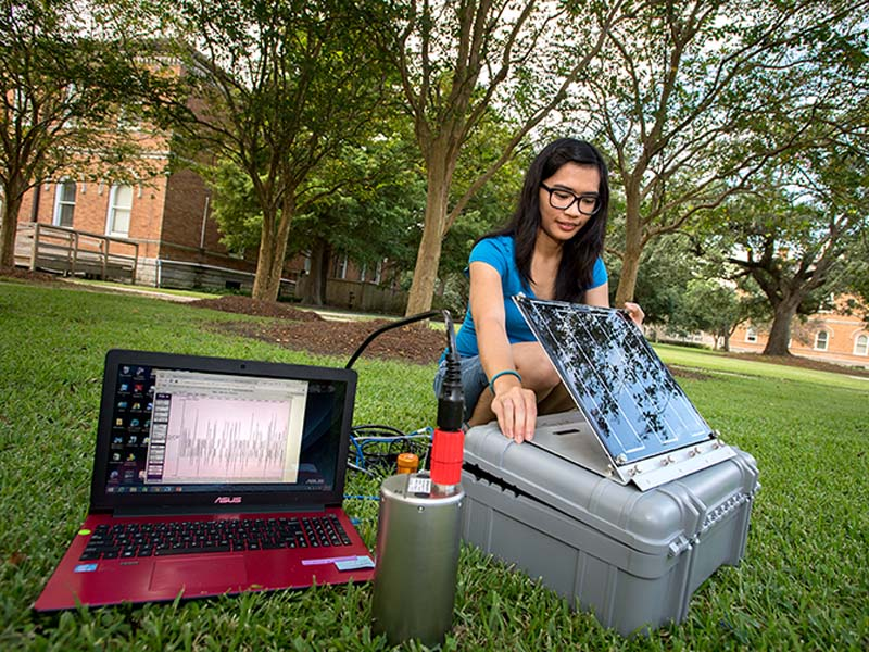 Sarah Oliva, a PhD student in earth and environmental sciences tests a seismometer in the quad near Blessey Hall. The state of the art equipment is headed for New Zealand where it will monitor unusual volcanic earthquakes.