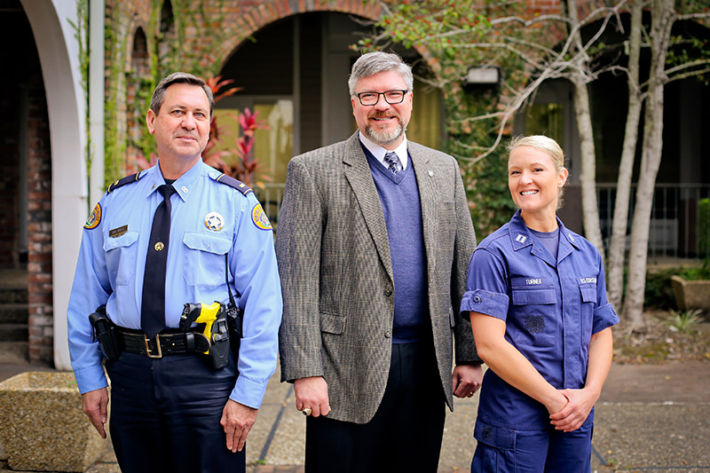 Graduates Lieutenant Mark Mulla (left) of the New Orleans Police Department and Lieutenant Marina Turner (right) from the United States Coast Guard stand with Michael Wallace (center), director of Tulane's Emergency and Security Studies