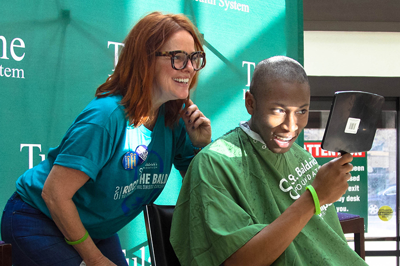 Second-year Tulane med student Elikem Dorbu gets his head shaved by stylist Suzanne Ensch