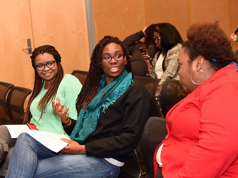Event attendees speak with Brittney Cooper (red jacket)