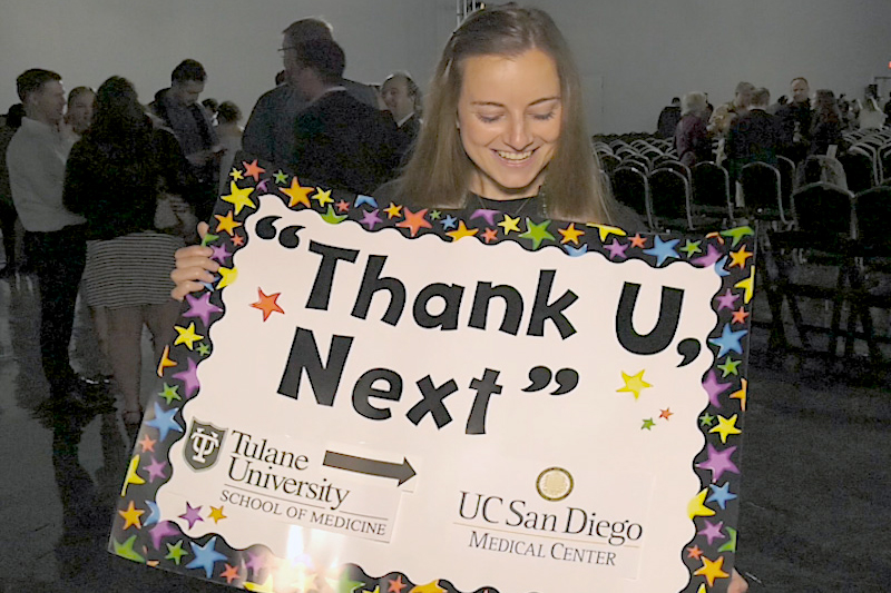A student holds a sign reading 'Thank U, Next' at Match Day 2019