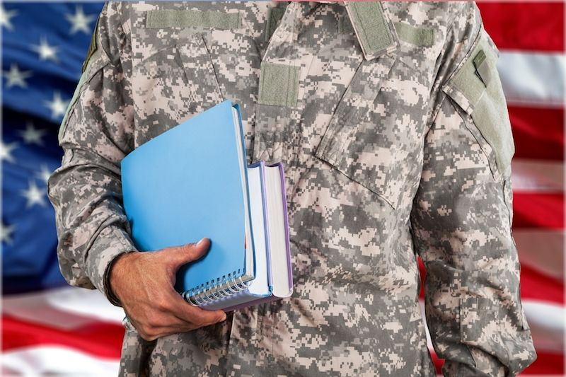 Photo of a serviceman carrying books in front an American flag