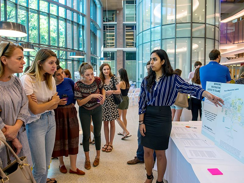 Ishanya Narang, right, discusses ways to create justice for survivors of sexual assault during a poster session.