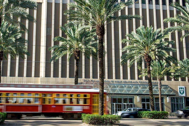 A streetcar zooms past the Tidewater Building, home of the School of Public Health and Tropical Medicine