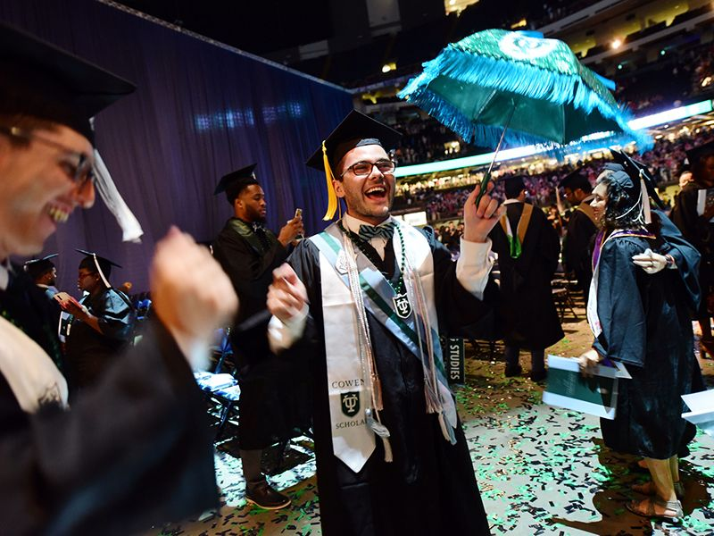 A graduate celebrates with a second-line umbrella at the end of the Unified Commencement ceremony