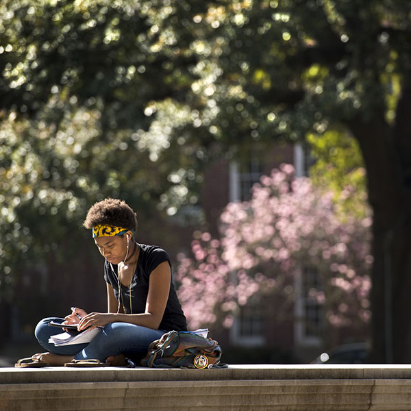 A student sits outside on campus with her books.