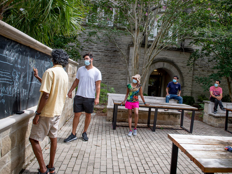 Masked students and professor engage in an outdoor class