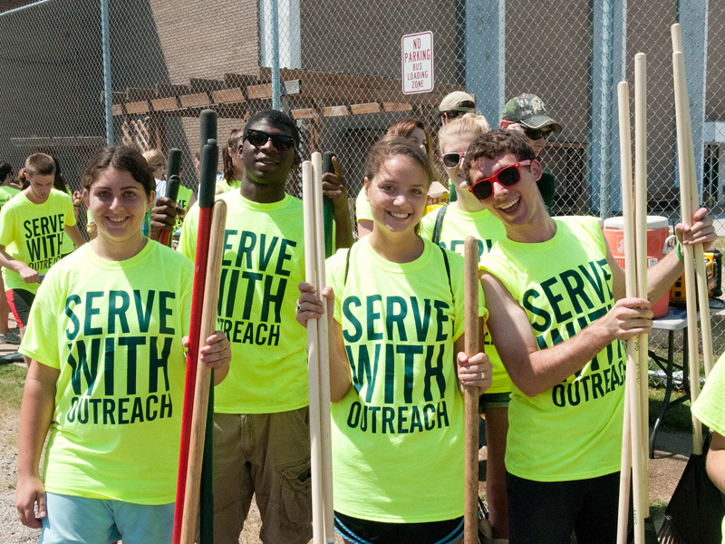 Students wearing Serve with Outreach tees pose for a photo at the Outreach Tulane service event