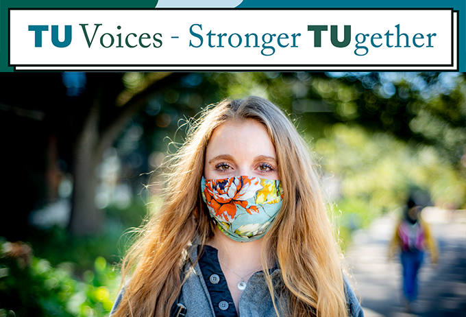 Student looking at camera wearing mask on campus with Stronger Together banner at top of image