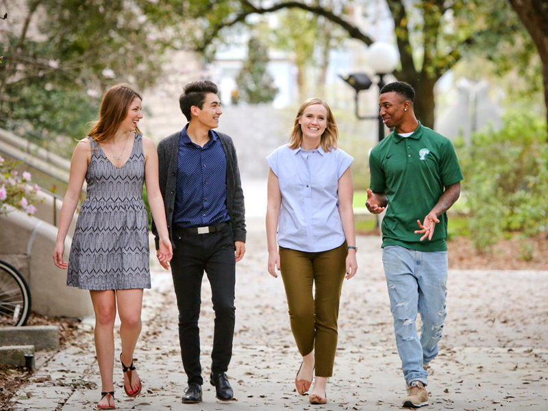 Four students talk and walk on campus