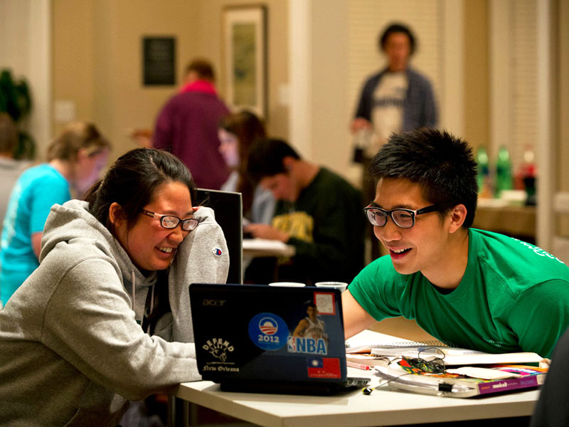 A pair of students shares a laugh over something on a laptop