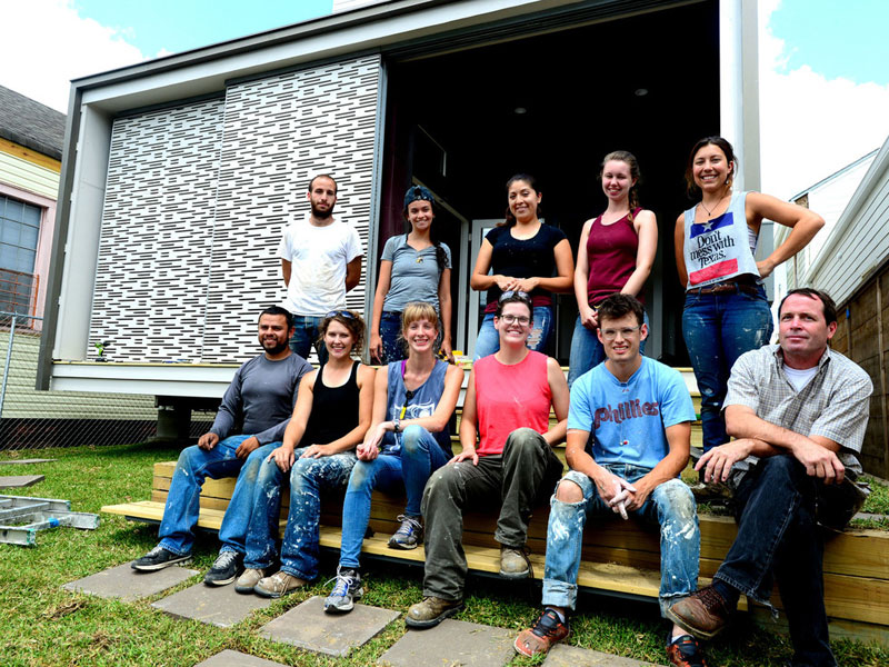 Students and teachers sit for a group photo in front of a structure they built.